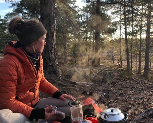 Ingeborg Austrått sitter ved stromkjøkken i skogen
