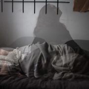 Kvinne sover under pledd, men gjenskinn av henne sitter oppreist