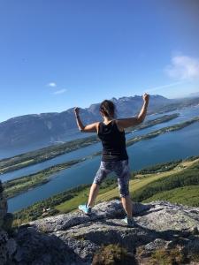 Kvinne i treningstøy med armene i været med flott sjøutsikt foran seg