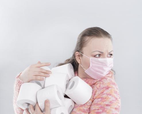 Kvinne med munnbind holder haug med doruller