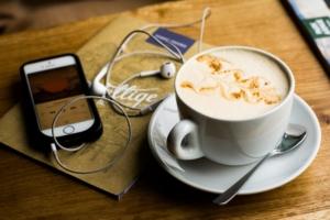 Telefon med øretelefoner og kaffekopp