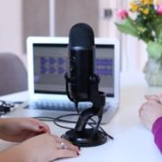 To mennesker med en laptop og mikrofon i midten