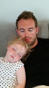 Mann og datter sover sittende på sofaen