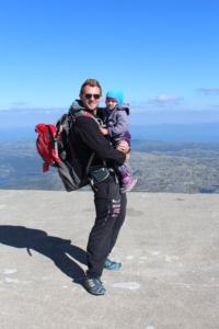 Stian Tollisen med barn i armene på toppen av et fjell