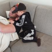 Stian Tollisen lukker øynene på sofa med sønnen som vil vise noe