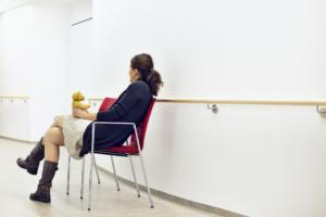 Kvinne med bamse venter i sykehuskorrdor