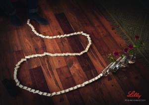 Bord med dominobrikker som har veltet og velter tre vaser med roser