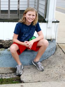 Ung gutt sitter i shorts med knærne eksponert