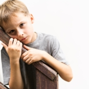 Ung gutt lent inntil trappegelender og er trist